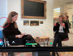 View through a camera lens showing Global Digital Women founder, Tijen Onaran and DHL Consulting CEO, Sabine Mueller, sitting in a modern office carrying out an interview on the topic 'personal branding'.
