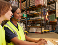 two women working on a computer in a warehouse