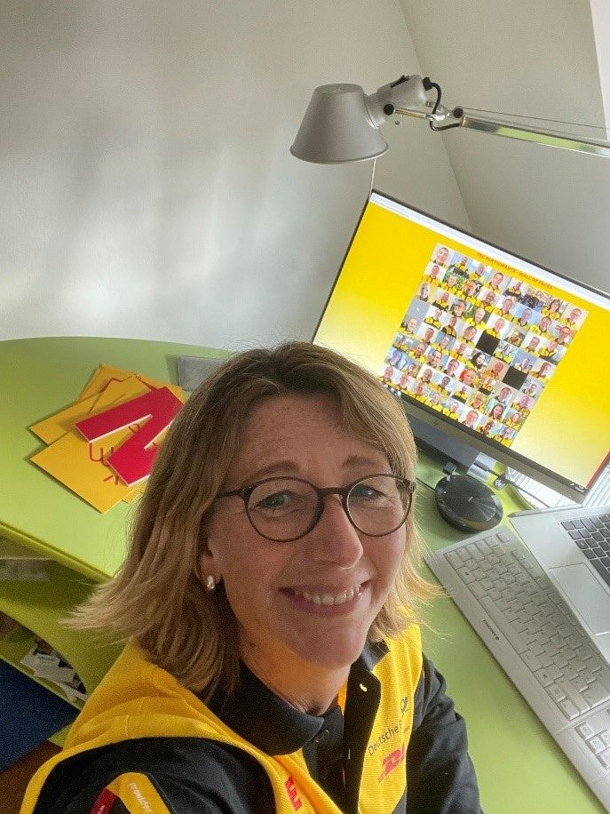 Sabine Mueller, CEO DHL Consulting, taking a selfie while sitting at her home office desk on a call with colleagues.